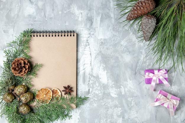 상위 뷰 노트북 말린 레몬 조각 아니스 소나무 나뭇가지 회색 배경에 작은 선물