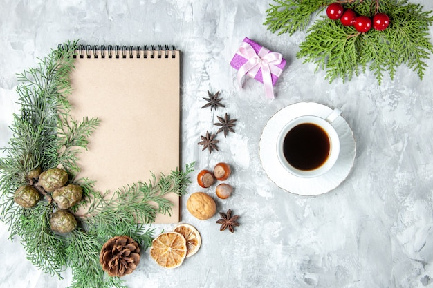 Top view notebook dried lemon slices anises pine tree branches walnut hazelnut cup of tea on grey surface