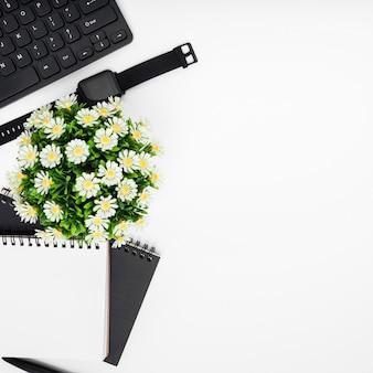 Cornice di fiori e taccuino vista dall'alto
