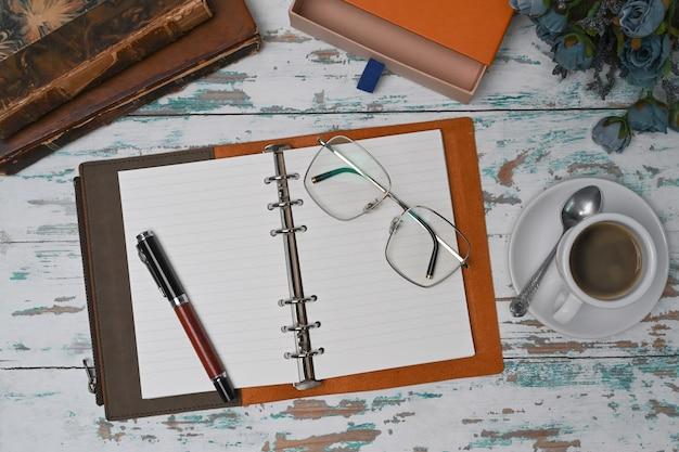 Тетрадь сверху, очки и кофейная чашка на деревянном столе.
