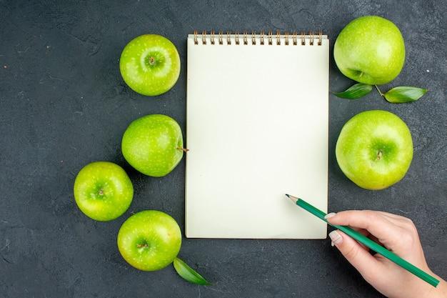 Вид сверху ноутбук зеленые яблоки зеленый карандаш в женской руке на темной поверхности