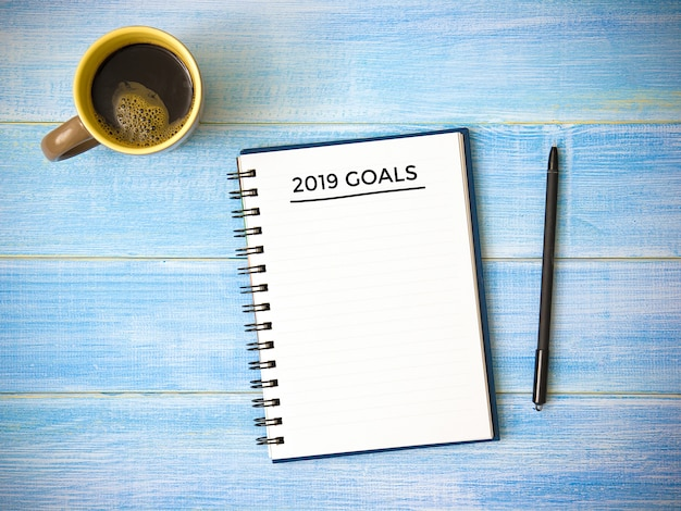 Top view of notebook handwriting goals 2019 year on blue wooden table.