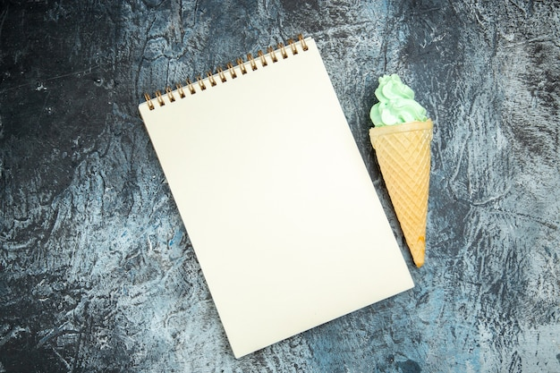 Top view a notebook and ice cream on dark background