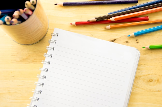 Top view notebook paper. colorful colored pencils on wooden table.