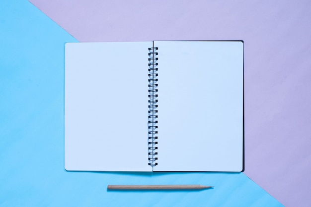 Top view of notebook and pencil on blue and pink pastel color bakcground