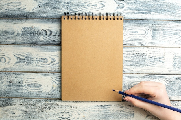 Top view notebook pencil in female hand on wooden surface
