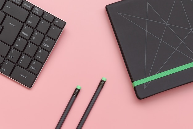 Top view, notebook and pencil with keyboard on pink background.