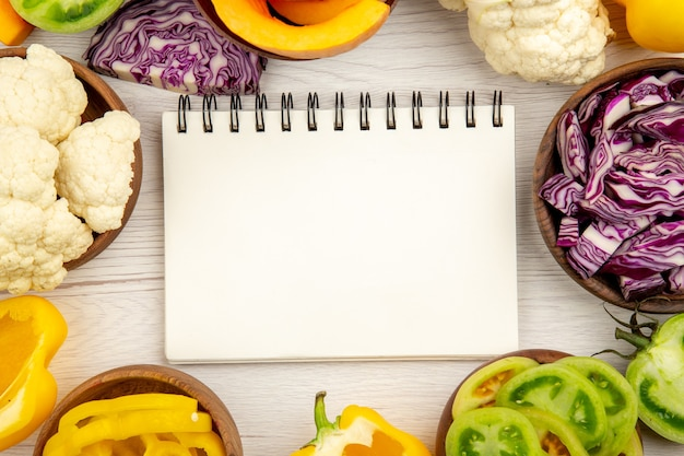 Top view notebook red cabbage in bowl cauliflower yellow bell pepper green tomato on white wooden surface