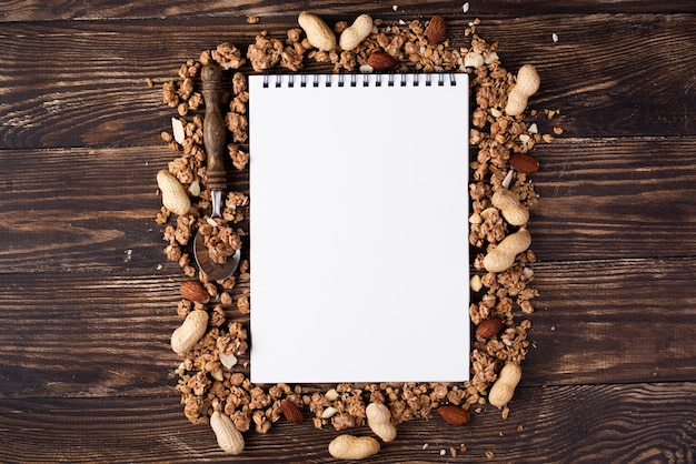 Top view of notebook surrounded by breakfast cereal with assortment of nuts