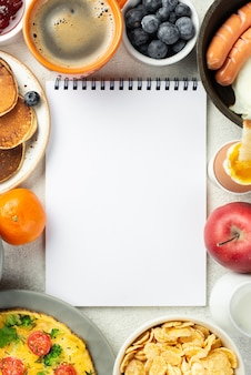 Top view of notebook surrounded by breakfast food