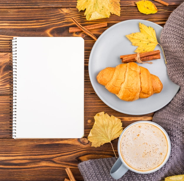Top view notebook surrounded by coffee and croissant