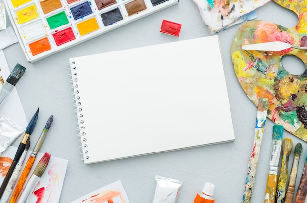 Top view notebook surrounded by painting elements
