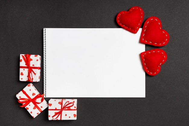 Top view of notebook surrounded with gift boxes and hearts