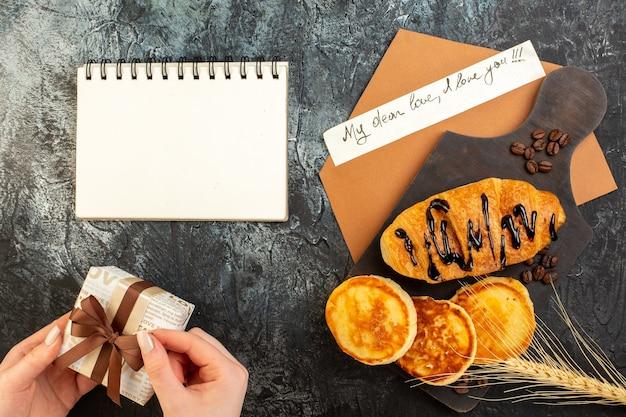 Vista dall'alto del taccuino e gustosa colazione con croissant di frittelle e confezione regalo con apertura a mano sul tavolo scuro