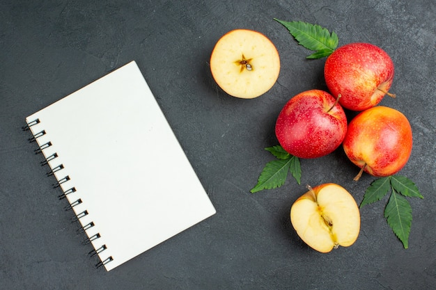Top view of notebook and whole cut fresh red apples and leaves on black background