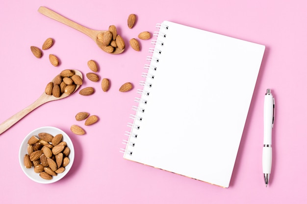Top view of notebook with almonds and pen
