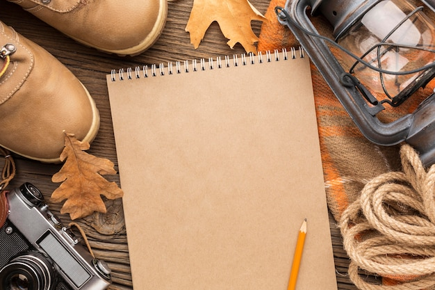 Top view of notebook with autumn leaves and boots