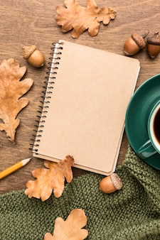 Top view of notebook with autumn leaves and coffee