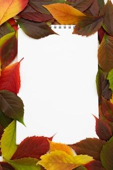 Vista dall'alto del taccuino con cornice di foglie d'autunno