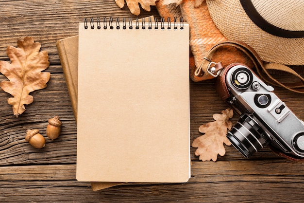 Top view of notebook with autumn leaves and hat