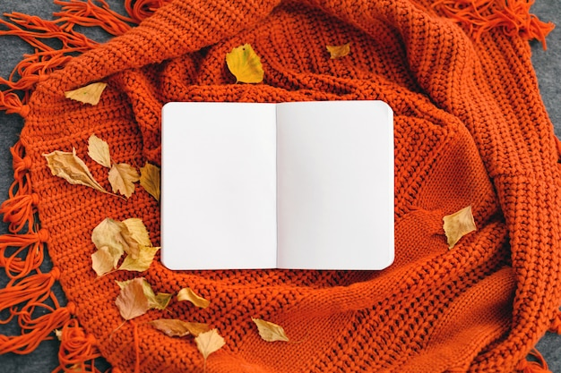 Top view of a notebook with autumn leaves on reddish knittted background. mock up.