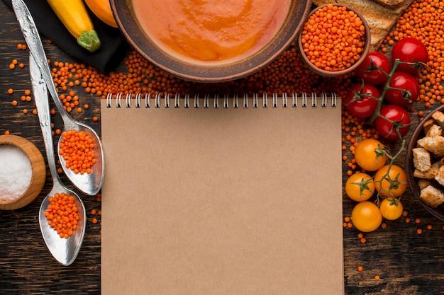 冬カボチャのスープのボウルとトップビューノートブック