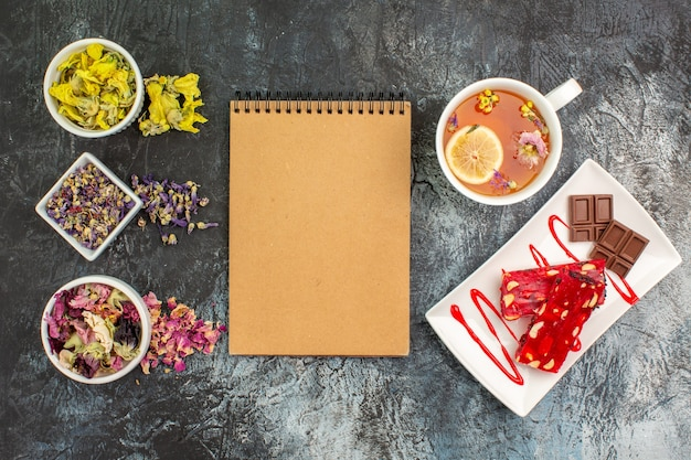 Top view of notebook with bowls of dry flowers and a cup of tea near a plate of chocolate