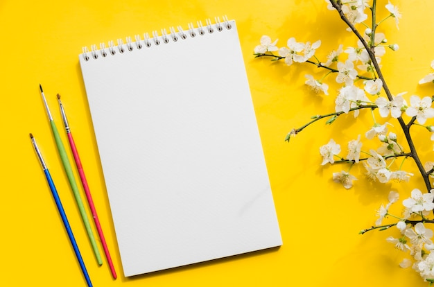 Top view notebook with branch of flowers