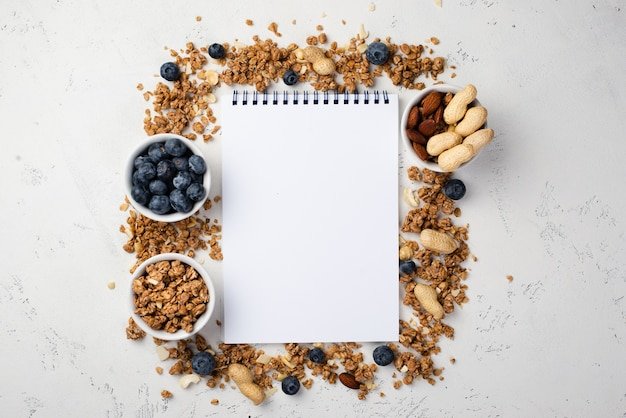 Top view of notebook with breakfast cereal and blueberries