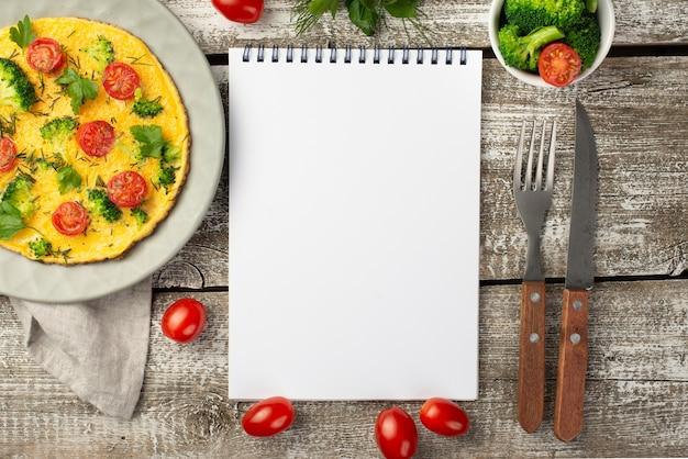 Top view of notebook with breakfast omelette and tomatoes