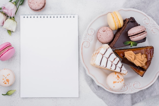 Top view of notebook with cake on plate and macarons