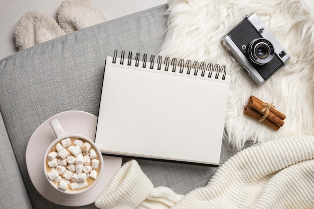 Top view of notebook with camera and cup of hot cocoa with marshmallows