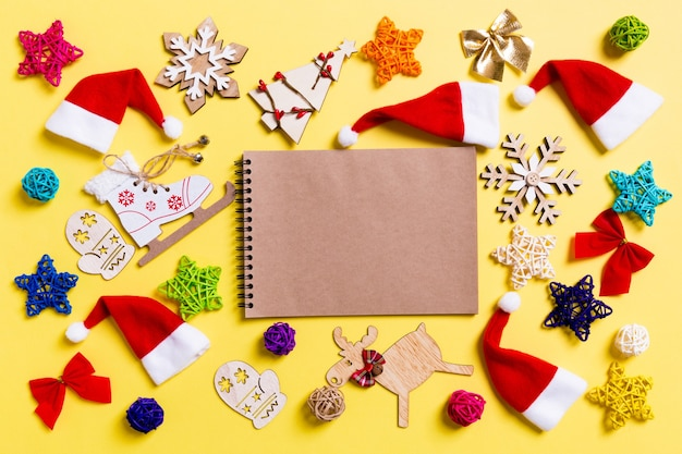 Top view of notebook with christmas decorations and santa hats on yellow background. happy holiday concept.