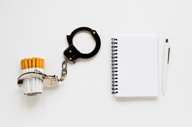 Top view notebook with cigarette and handcuffs