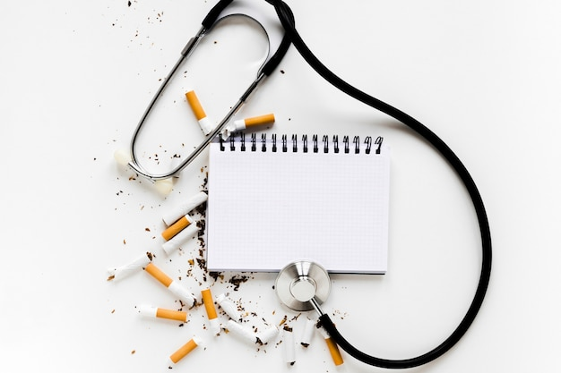 Top view notebook with cigarettes and stethoscope