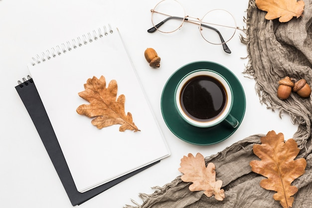 Top view of notebook with coffee and autumn leaves
