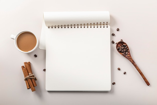 Top view of notebook with coffee cup and cinnamon sticks