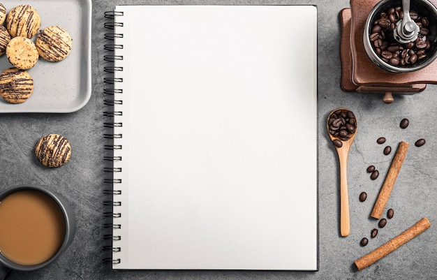 Top view of notebook with coffee grinder and cookies