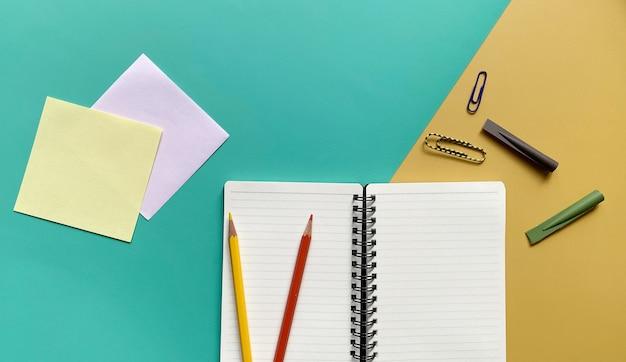 緑と黄色の背景に色鉛筆ペーパークリップと鉛筆キャップとトップビューノートブック