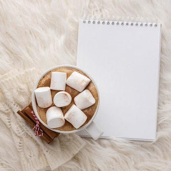 Top view of notebook with cup of hot cocoa with marshmallows