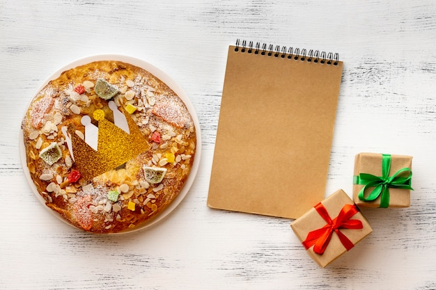 Top view of notebook with dessert and presents for epiphany day