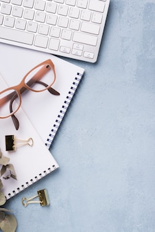 Top view of notebook with dried leaves and glasses on desk