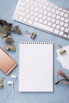 Top view of notebook with dried leaves and smartphone on desk