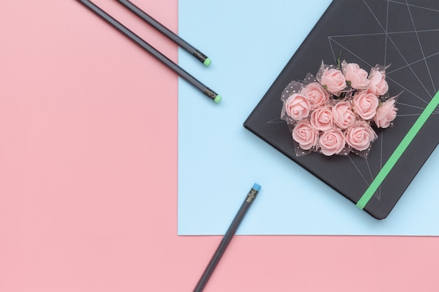 Top view, notebook with flowers and pencil on blue and pink background.