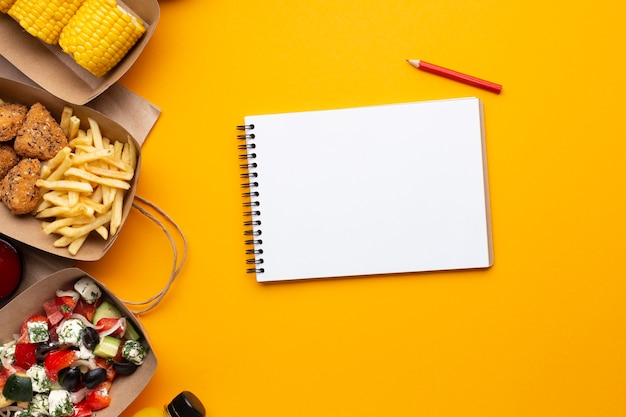 Top view notebook with food on yellow background