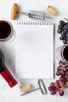 Top view notebook with frame of grapes and wine