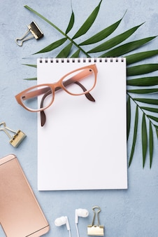 Top view of notebook with glasses and leaves on desk