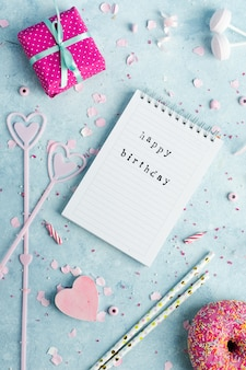 Top view of notebook with happy birthday wish and present