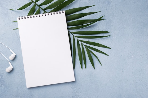 Top view of notebook with headphones and leaves on desk