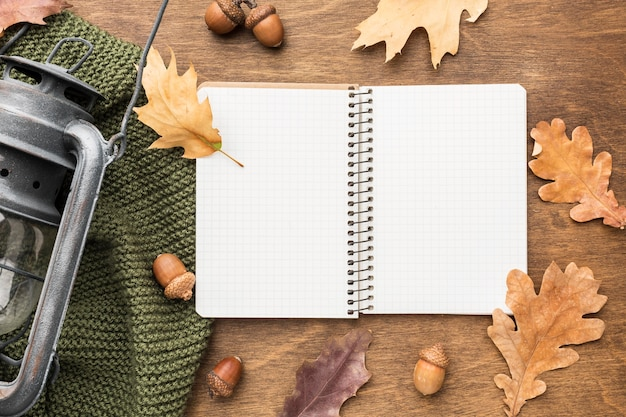 Top view of notebook with lantern and autumn leaves
